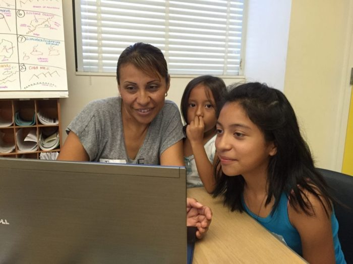 Mother and her two daughters in front of a laptop
