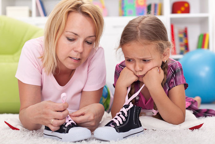 Mother teaching daughter to tie shoelaces