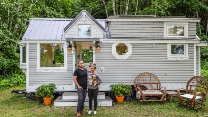 couple standing in front of tiny house